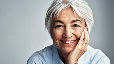 Older woman with short gray hair smiling at the camera